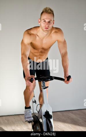 Attraktive junge Mann trainieren im Fitnessraum, spinning auf Heimtrainer - Stockfoto
