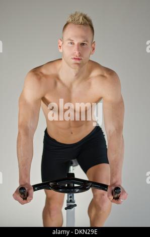 Attraktive junge Mann trainieren im Fitnessstudio: Spinnen auf Heimtrainer - Stockfoto