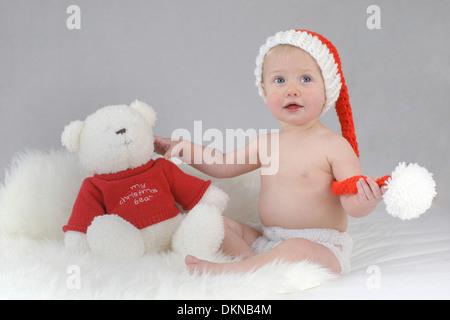 Ein Baby tragen einer Weihnachtsmütze mit ihrem Weihnachtsbär - Stockfoto