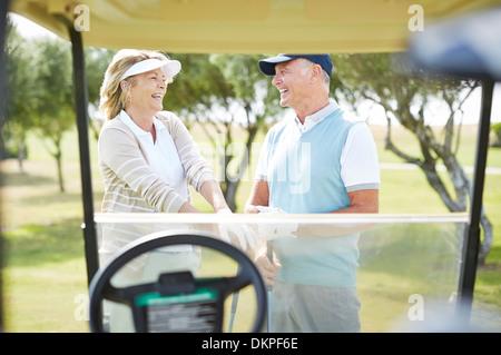 Älteres paar lachend auf Golfplatz - Stockfoto