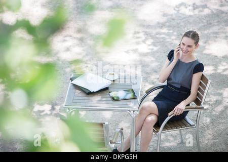 Geschäftsfrau im Straßencafé sitzen - Stockfoto