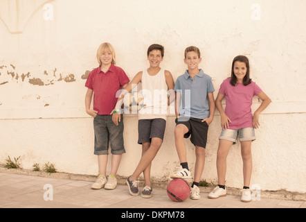 Kinder mit Fußbällen Wand gelehnt - Stockfoto