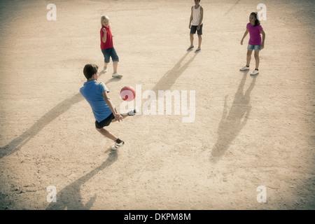 Mit Fußball im Sand spielende Kinder