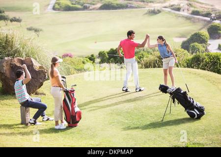 Freunde spielen Golf auf Kurs - Stockfoto
