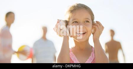 Anhören von Muscheln am Strand Mädchen - Stockfoto