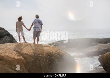 Älteres Paar halten die Hände auf Felsen am Strand - Stockfoto