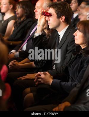 Mann mit Opernglas in Theater-Publikum - Stockfoto