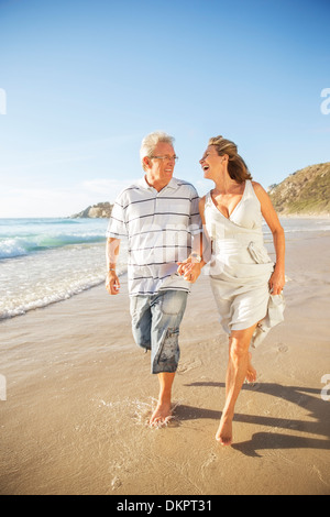Älteres Paar in Brandung am Strand zu Fuß - Stockfoto