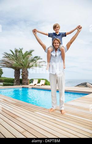 Vater mit Sohn auf Schultern am Pool - Stockfoto