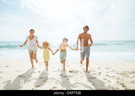 Familie läuft zusammen am Strand - Stockfoto