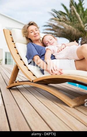 Ältere Frau und Enkelin entspannen im Liegestuhl - Stockfoto