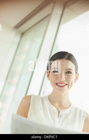 Geschäftsfrau, die lächelnd im Büro - Stockfoto