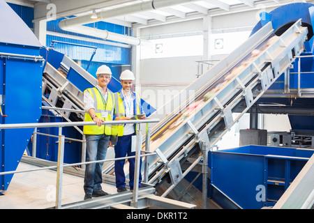 Arbeitnehmer, die lächelnd im recycling-center - Stockfoto
