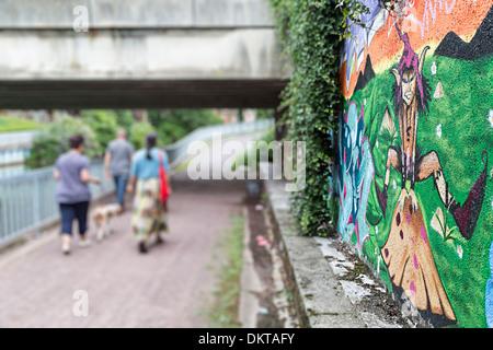 Menschen gehen unter Brücke neben Graffiti-Kunst von Pixie, Douai, Nord-Pas-de-Calais, Frankreich - Stockfoto