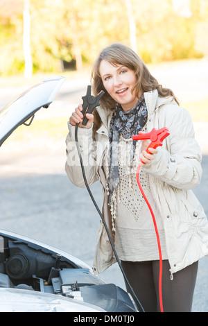 Schöne Frau Booster Anschlusskabel an eine Autobatterie - Stockfoto