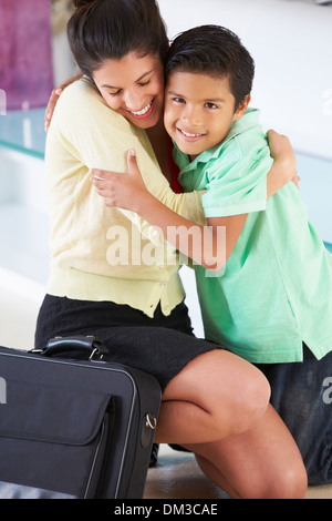 Sohn begrüßt Mutter, nach Rückkehr von der Arbeit - Stockfoto