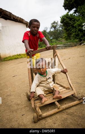 Kinder spielen mit einem hausgemachten Kinderwagen (Buggy) in Vatomandry Bezirk, Madagaskar. - Stockfoto