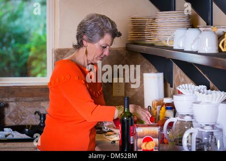 Reife Frau, Kaukasier, 59 Jahre alt, ist Zubereitung von Snacks in ihrer Küche für eine Grillparty. - Stockfoto