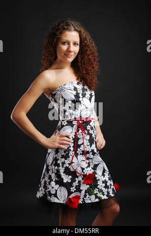 Krauses Mädchen in ein Cocktail-Kleid - Stockfoto
