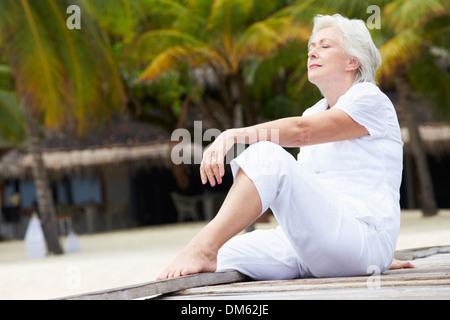 Senior Woman Sitting On Holzsteg - Stockfoto