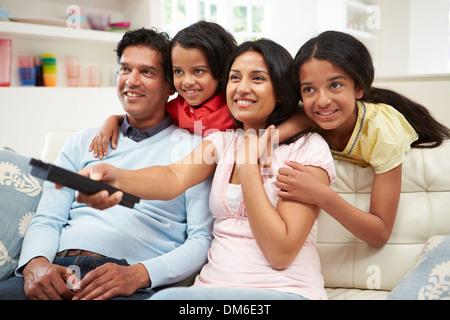 Indische Familie sitzt auf dem Sofa vor dem Fernseher zusammen - Stockfoto