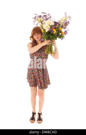 Attraktive rote Mädchenakt stehend mit großen Strauß Blumen im windigen Studio isoliert auf weißem Hintergrund - Stockfoto