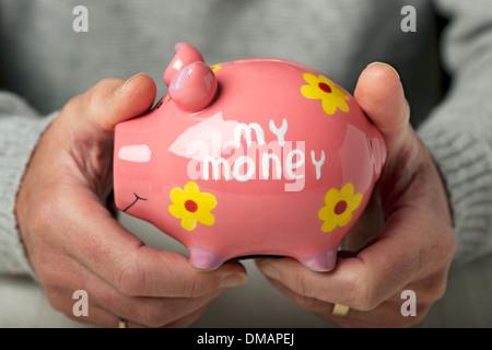 Hände halten piggy Bank England UK Vereinigtes Königreich GB Grossbritannien - Stockfoto
