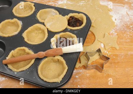 Vorbereitung Mince Pies, süßes Gebäck und Mince Pie Zutaten auf einem Backblech auf eine hölzerne Arbeitsplatte - Stockfoto