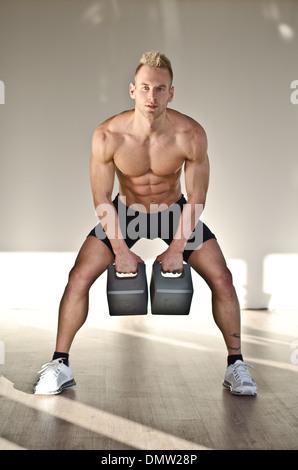 Muskulösen jungen Mann Hemd im Fitness-Studio-Training mit Kettlebells, Blick in die Kamera - Stockfoto