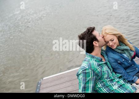 Ein Mann und eine Frau sitzend auf einem Steg am See. - Stockfoto