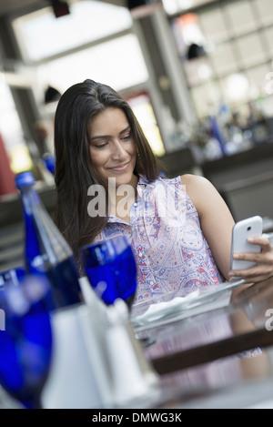 Ein Café-Interieur. Eine Frau mit einem Smartphone. - Stockfoto