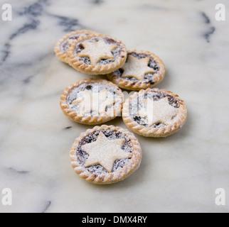 Sechs hausgemachten Puderzucker bestäubt Mince Pies auf grauem Marmor Oberfläche - Stockfoto