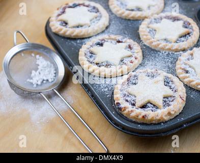Hausgemachte Zuckerglasur bestäubt Mince Pies im Backblech mit Sieb auf Holzuntergrund - Stockfoto
