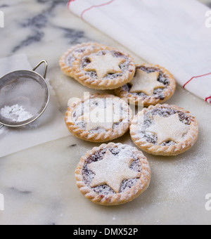 Hausgemachte Zuckerglasur bestäubt Mince Pies auf grauem Marmor Oberfläche mit Sieb und weißen Tuch mit roten Nähten - Stockfoto