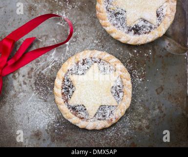 Hausgemachte Zuckerglasur bestäubt Mince Pies auf graue rustikale Oberfläche mit rotem Band - Stockfoto