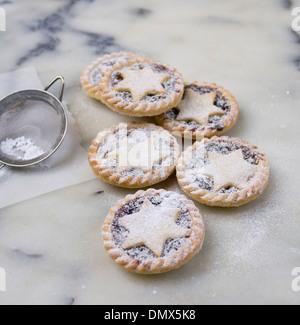 Hause aus Puderzucker bestäubt Mince Pies auf einer grauen Marmor Oberfläche - Stockfoto