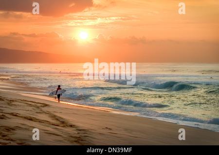 HAWAII, OAHU - Tropical Sunset mit Surfer Wandern am Ufer des Sonnenuntergang - Stockfoto