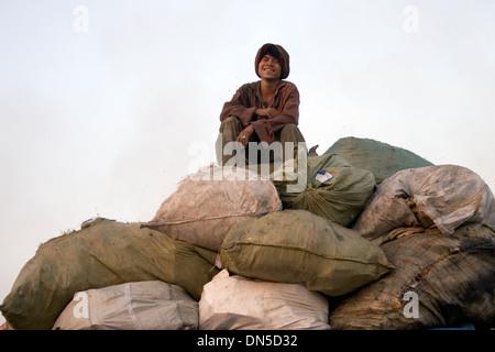 Ein Mann sitzt auf der Oberseite einen großen Haufen von Müll-Säcke bei der Stung Meanchey Mülldeponie in Phnom - Stockfoto