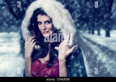 Frau im Umhang mit Kapuze stehen auf bewaldeten Pfad im Schnee
