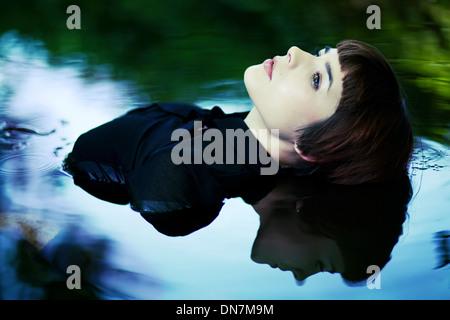 Junge Frau sitzt im Wasser, Porträt Stockfoto