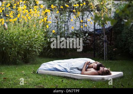 Liebespaar liegt schlafend auf einer Matratze im Garten