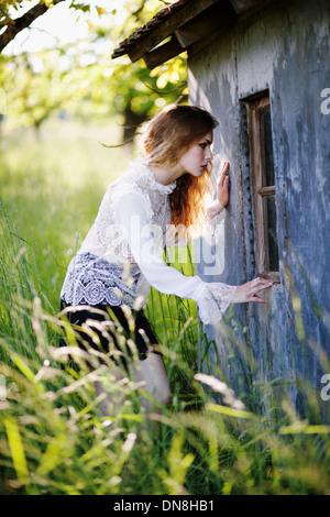 Junge Frau schaut in das Fenster einer Hütte - Stockfoto
