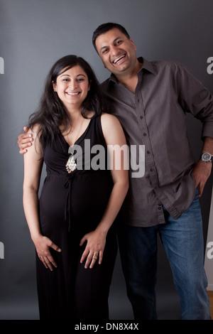 Ein Ost-indischen Mann umarmt seine schwangere Frau trägt ein Kleid - Stockfoto