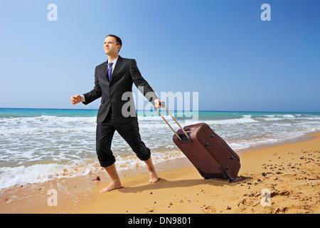 Junger Geschäftsmann im Anzug an einem Sandstrand mit seinem Gepäck zu Fuß - Stockfoto