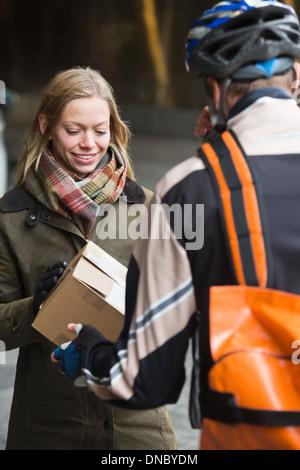 Junge Frau, die eine Paket empfangen - Stockfoto