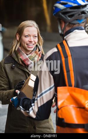 Lächelnde junge Frau erhält eine Paket von Courier Lieferung Ma - Stockfoto