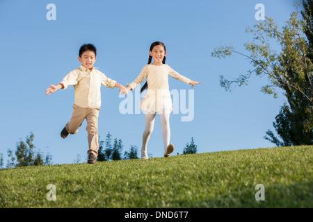 Niedliche kleine Mädchen und jungen in einem Park zu fliegen - Stockfoto