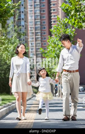 Junge Eltern mit Tochter spazieren am Bürgersteig einher - Stockfoto