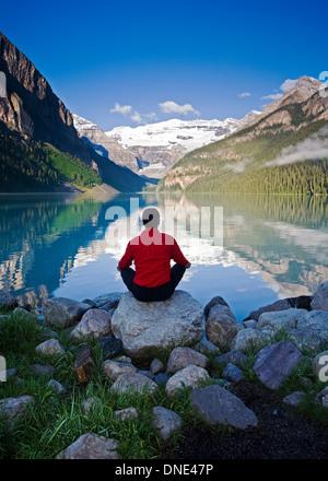 Mittleren Alters, Männlich meditieren auf Felsen am Lake Louise, Alberta, Kanada. - Stockfoto