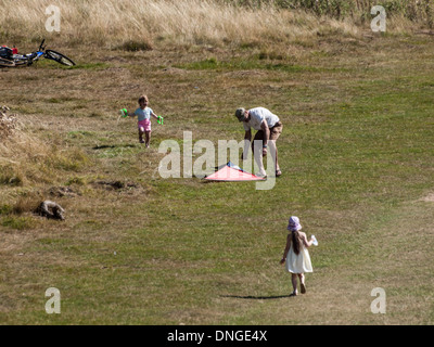 Ein Vater und seine Kinder haben Spaß mit einem Drachen an einem warmen Sommertag im Richmond Park, London. - Stockfoto